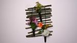 """Eine Wanddekoration für die Küche oder Flur wird dir in diesen Beitrag vorgestellt. Hierfür benötigst du: 14 gerade Weiden- Ast- Teile ohne Verzweigungen etwa 30cm Lang, Wollfaden (Braun oder Schwarz), drei Röhrchen (Orchideenröhrchen), Silberdraht und Sekundenkleber. Die Gestaltung der Röhrchen kann je nach Jahreszeit unterschiedlich ausfallen. Wir haben uns jetzt für einfache Gartenblumen entschieden, ihr könnt selbstverständlich auch Anthurien oder Orchideen verwenden, je nach deinen Vorlieben. Die Arbeitsschritte sind: 1. Äste in leicht unterschiedlichen Abständen mit dem Wollfaden miteinander verbinden und jeweils mit einem Knoten befestigen. 2. Röhrchen mit Wollfaden umwickeln und mit dem Sekundenkleber fixieren. 3. Röhrchen mit Draht (Schlaufe) an dem Gestell befestigen. Weitere Deko Ideen findest du auf dem youtube channel von """"Deko Ideen mit Flora-Shop"""" und über deine Kommentare oder Fragen zum Video würde ich mich sehr Freuen!"""