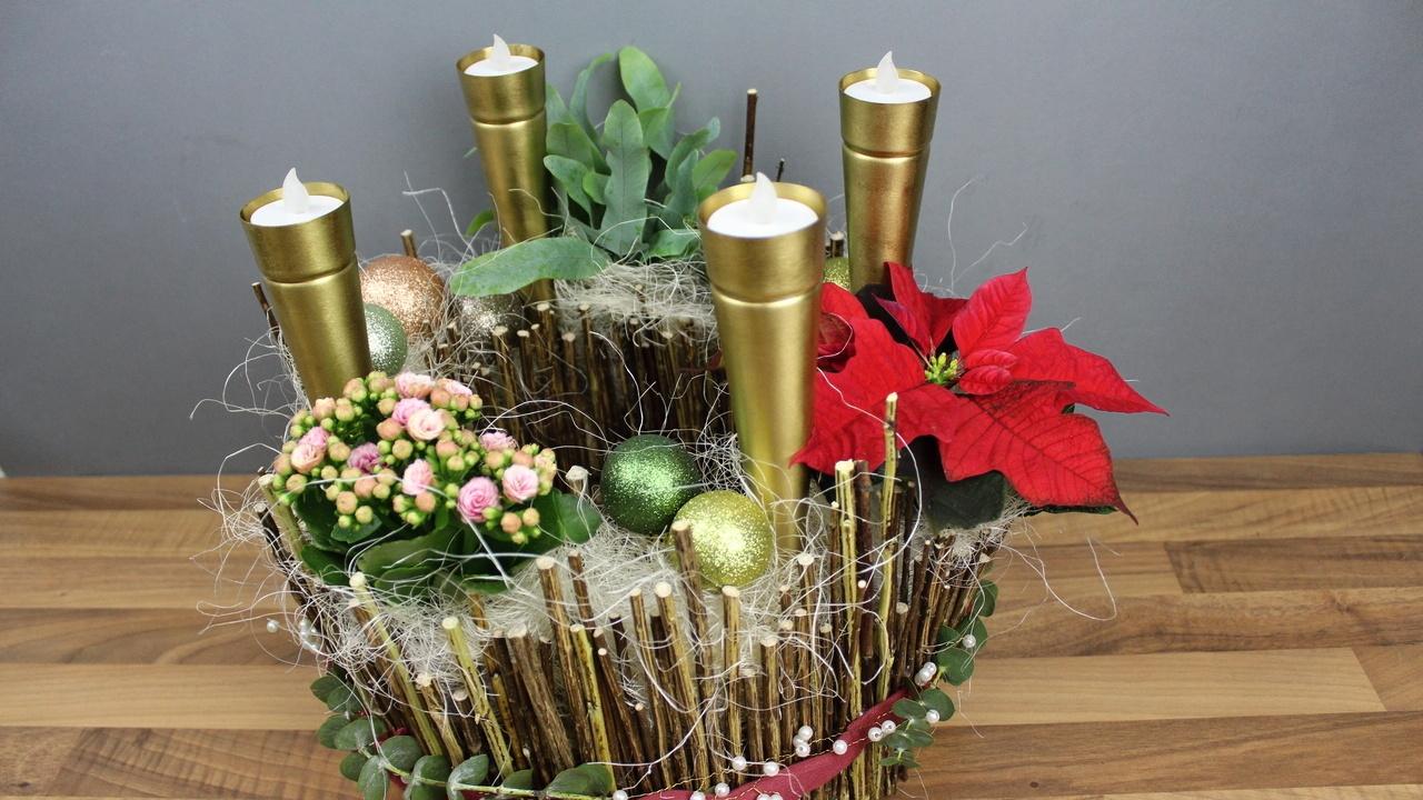 Moderner bepflanzter Adventskranz aus Naturmaterialien mit vier Kerzen